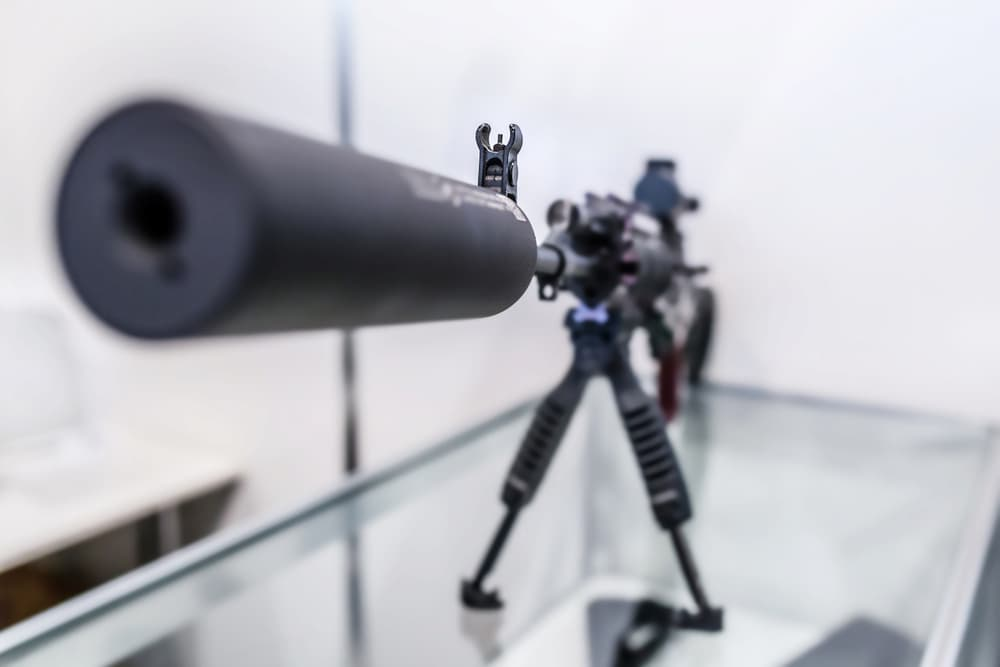 close up photo of gun with a suppressor